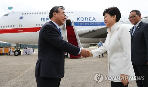 President Park Geun-hye (R) shakes hands with Lee Jung-hyun, leader of the ruling Saenuri Party, before she boards her plane at the military airport in Seongnam, just south of Seoul, on Sept. 2, 2016, to depart for Russia's Far East port city of Vladivostok. There she will attend an economic forum and a summit with her Russian counterpart Vladimir Putin. Park's visit to Russia is as part of her eight-day trip that will also takes her to China and Laos. (Yonhap)