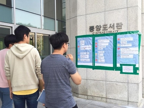 Students look at posters put up outside a library by a student council of Seoul's Yonsei University on Sept. 1, 2016. The student council revealed a group chat of 30 male students verbally harassing fellow female students. (Yonhap)