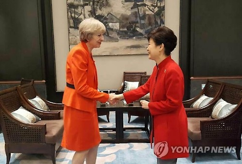 This photo, provided by South Korea's presidential office Cheong Wa Dae on Sept. 4, 2016, shows President Park Geun-hye (R) shaking hands with British Prime Minister Theresa May before their talks on the sidelines of the Group of 20 leading economies in Hangzhou, eastern China. (Yonhap)