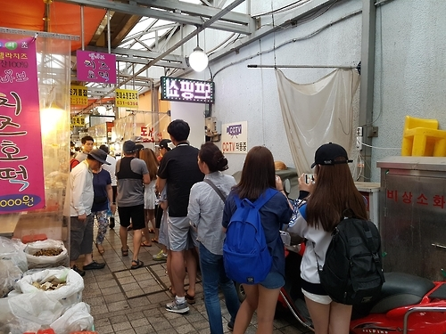 "A group of people stand in a queue to buy cheese-stuffed ""hodduk"" at Sokcho Tourist Fish Market in Sokcho, South Korea, on July 18, 2016. (Yonhap)"