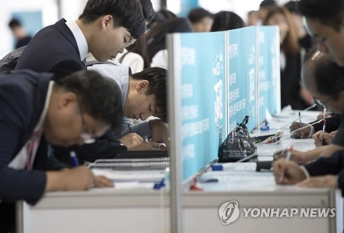Job seekers prepare documents at a startup company job fair at COEX in Seoul on Oct. 6, 2016. (Yonhap)