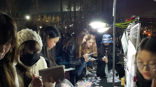 "Global fans of South Korean boy group Bangtan Boys, or BTS, browse street kiosks selling souvenirs with pictures of BTS after watching ""BTS 3RD MUSTER [ARMY.ZIP+]"" in Gocheok Skydome, southwestern Seoul, on Nov. 13, 2016. (Yonhap)"