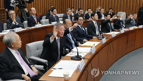 In the file photo, taken on Dec. 6, 2016, Kim Seung-youn (third from L, front row) and others raise their hands to express their opposition to dissolving the FKI during a special parliamentary hearing in Seoul. (Yonhap)