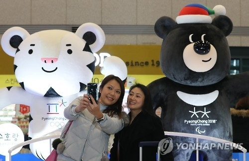 Two women photograph themselves with the mascots for the 2018 Winter Olympics -- the white tiger Soohorang (L) and the Asiatic black bear Bandabi -- in the background at the arrival area of Incheon airport, west of Seoul, on Jan. 4, 2017. The 2018 Olympic Winter Games will kick off on Feb. 9, 2018, in the eastern South Korean resort town of PyeongChang. (Yonhap)