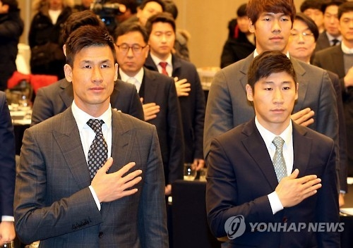 Gangwon FC forwards Jung Jo-gook (L) and Lee Keun-ho salute the national flag during Gangwon's kickoff meeting for the 2017 season at a hotel in Gangneung, Gangwon Province, on Jan. 5, 2017. (Yonhap)