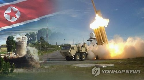 In this undated captured image from Yonhap News TV, a THAAD system (R) is shown firing an interceptor and a nuclear facility in North Korea against its national flag. (Yonhap)