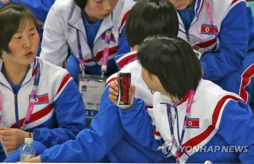 A North Korean women's hockey player holds a can of Coca-Cola while chatting with her teammate during the game between South Korea and Slovenia at the International Ice Hockey Federation Women's World Championship Division II Group A at Kwandong Hockey Centre in Gangneung, Gangwon Province, on April 2, 2017. (Yonhap)