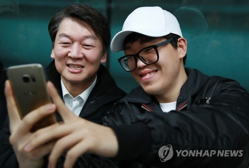 Ahn Cheol-soo (L), the presidential nominee of the centrist People's Party, takes a selfie with a passenger on the subway in Seoul on April 5, 2017. (Yonhap)