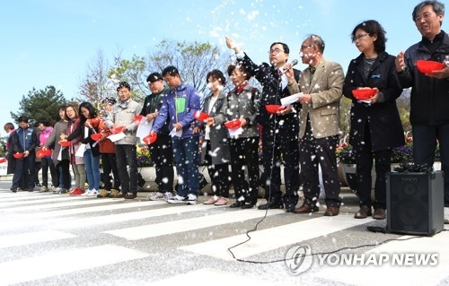 Dozens of liberal civic activists throw salt in a traditional act of showing disgust at a protest rally held April 10, 2017, in Changwon, South Gyeongsang Province over former governor Hong Joon-pyo's belated resignation that effectively prevented a by-election to pick his successor. (Yonhap)