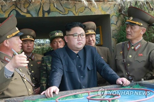 This photo carried by the Rodong Sinmun, North Korea's main newspaper, on May 5, 2017, shows North Korean leader Kim Jong-un (C) inspecting military detachments on two islets in waters off the country's southwest front. (For Use Only in the Republic of Korea. No Redistribution) (Yonhap)