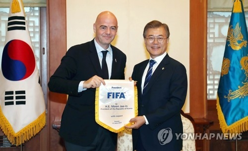 In this photo provided by South Korean presidential office Cheong Wa Dae, South Korean President Moon Jae-in (R) poses with FIFA President Gianni Infantino after their meeting on June 12, 2017. (Yonhap)