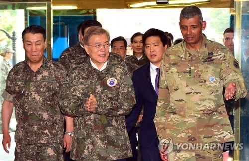 South Korean President Moon Jae-in enters the headquarters of the South Korea-U.S. Combined Forces Command (CFC) in Seoul on June 13, 2017, flanked by CFC commander Gen. Vincent K. Brooks (R) and its deputy commander Gen. Leem Ho-yong. (Yonhap)