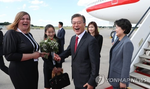 South Korean President Moon Jae-in (third from L) and his wife, Kim Jung-sook (R), are greeted by German officials after their arrival in Hamburg on July 6, 2017, for the upcoming G20 summit in the German port city. (Yonhap)