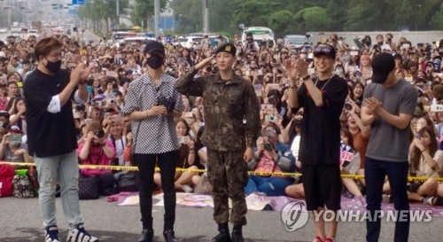 In this photo released by Label SJ, Eunhyuk (C), a member of the K-pop boy group Super Junior, salutes in front of a military unit in Wonju, east of Seoul, on July 12, 2017, after being discharged from military service. (Yonhap)