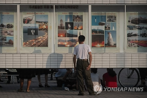 A Pyongyang citizen looks at posters of missile launches on July 25, 2017. (AFP-Yonhap)