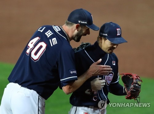 Dustin Nippert of the Doosan Bears (L) chats with second baseman Oh Jae-won after completing a scoreless sixth inning against the Kia Tigers in Game 1 of the Korean Series at Gwangju-Kia Champions Field in Gwangju on Oct. 25, 2017. (Yonhap)