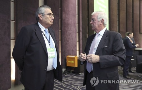 In this photo taken by the Associated Press on Nov. 16, 2017, International Olympic Committee Vice President Ugur Erdener (L) speaks with World Anti-Doping Agency (WADA) President Craig Reedie before the WADA Foundation Board Meeting in Seoul. (Yonhap)