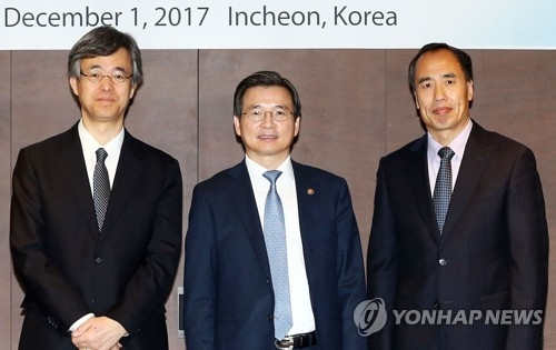 Ryozo Himino, vice minister for international affairs at Japan's Financial Services Agency (L); Kim Yong-beom, vice chairman of the Financial Services Commission (C); and Wang Zhaoxing, vice chairman of China's Banking Regulatory Commission, pose for the camera ahead of a meeting in Incheon, South Korea, on Dec. 1, 2017. (Yonhap)