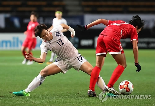 South Korea's Yoo Young-a (L) tries to take the ball away from North Korea's Ri Un-young during the women's football match between South Korea and North Korea at the East Asian Football Federation (EAFF) E-1 Football Championship at Soga Sports Park in Chiba, Japan, on Dec. 11, 2017. (Yonhap)