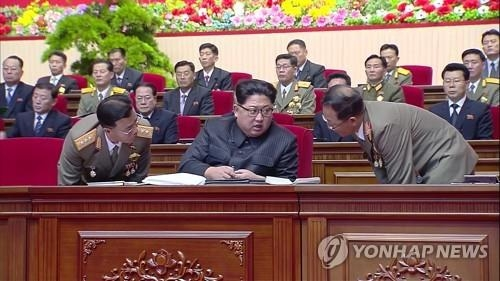 This photo captured from North Korea's Korean Central TV on Dec. 12, 2017, shows Jang Chang-ha (L) and Jon Il-ho (R) closely listening to Kim Jong-un during the 8th Conference of Munitions Industry. (For Use Only in the Republic of Korea. No Redistribution) (KCNA-Yonhap)