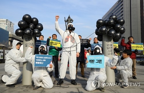 Environmental activists stage a performance to protest coal-fired power plants in downtown Seoul on Dec. 7, 2018. (Yonhap)
