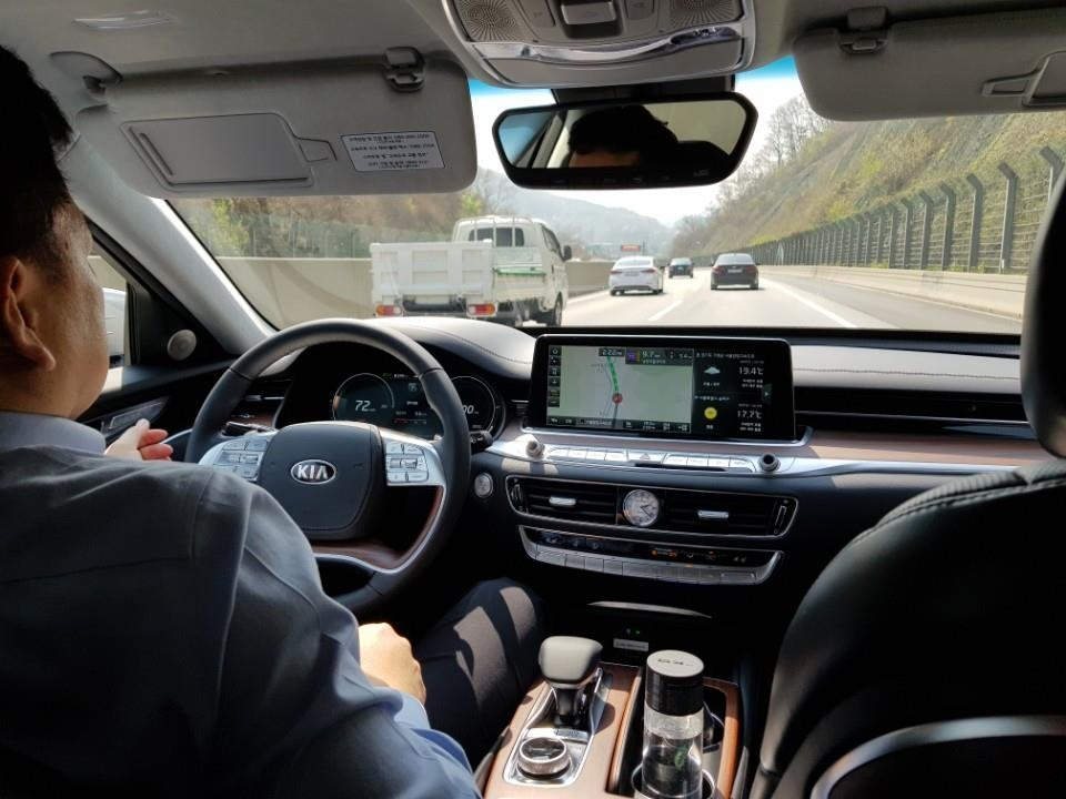 In this photo taken on April 17, 2018, a reporter tests the lane following assist function during a test drive event held near Seoul. (Yonhap)