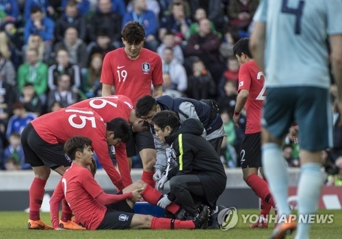 In this file photo taken March 24, 2018, South Korea's Kim Jin-su is inspected by team doctors during international football friendly between South Korea and Northern Ireland at Windsor Park in Belfast.