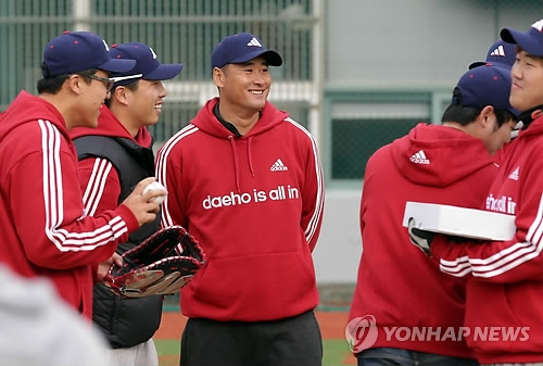 In this file photo from Nov. 23, 2012, former major league pitcher Baek Cha-seung (C) smiles during a youth baseball camp in Busan, 450 kilometers southeast of Seoul. (Yonhap)