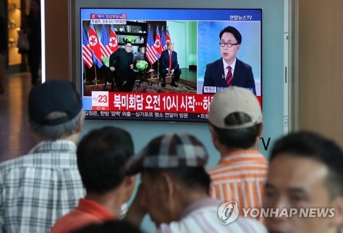 People watch TV news on the summit talks between U.S. President Donald Trump and North Korean leader Kim Jong-un at Seoul Station in Seoul on June 12, 2018. (Yonhap)