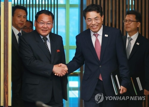 This photo provided by the Joint Press Corps shows South Korea's chief delegate Kim Jeong-ryeol (R) shaking hands with his North Korean counterpart Kim Yun-hyok before starting talks on railway cooperation at the truce village of Panmunjom on June 26, 2018. (Yonhap)