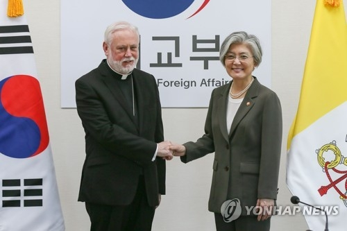 South Korean Foreign Minister Kang Kyung-wha (R) shakes hands with Archbishop Paul Richard Gallagher, the Vatican's secretary for relations with states, before their talks in Seoul on July 6, 2018, in this photo provided by Seoul's foreign ministry. (Yonhap)