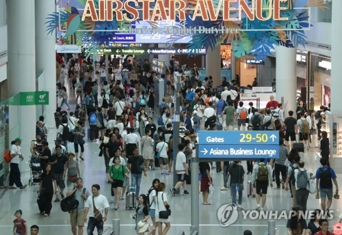 In this photo taken Aug. 5, 2018, a large number of travelers move through an area with duty-free shops on both sides at Incheon International Airport. (Yonhap)