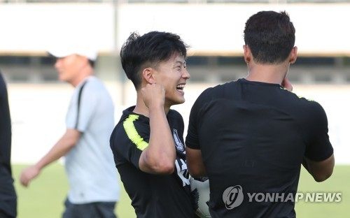 South Korean football forward Lee Seung-woo (L) smiles during the under-23 national football team's training at Paju Stadium in Paju, north of Seoul, on Aug. 8, 2018. (Yonhap)