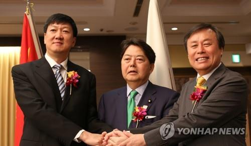 From left: Gao Zhidan, deputy director of the General Administration of Sport of China; Yoshimasa Hayashi, Japanese minister of sports; and Do Jong-whan, South Korean sports minister, hold hands after their trilateral meeting in Tokyo on Sept. 13, 2018. (Yonhap)