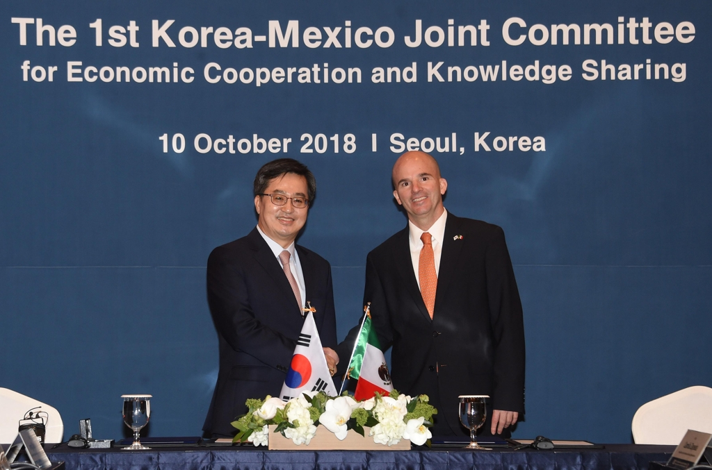 South Korean Finance Minister Kim Dong-yeon (L) shakes hands with his Mexican counterpart, Jose Antonio Gonzalez Anaya, before the 1st Korea-Mexico Joint Committee for Economic Cooperation and Knowledge Sharing, in Seoul, on Oct. 10, 2018. (Yonhap)