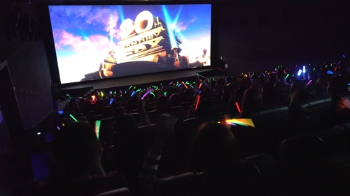 "This photo, provided by 20th Century Fox Korea, shows South Korean moviegoers waving glow-in-the-dark sticks in the singalong screening of ""Bohemian Rhapsody"" on Nov. 24, 2018. (Yonhap)."