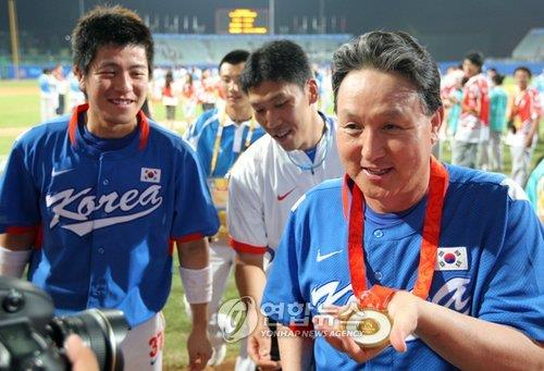 In this file photo from Aug. 23, 2008, Kim Kyung-moon (R), then manager of the South Korean national baseball team, holds the gold medal won at the Beijing Olympics after defeating Cuba 3-2 in the final at Wukesong Baseball Field in the Chinese capital. (Yonhap)