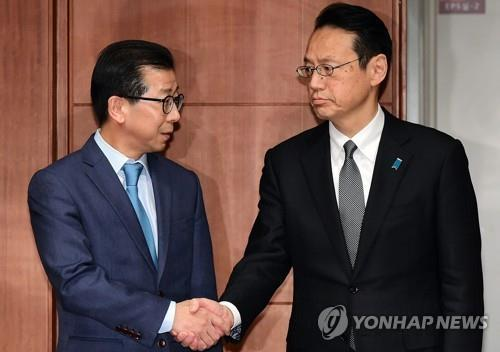 Kim Yong-kil (L), director general for Northeast Asian affairs at South Korea's Ministry of Foreign Affairs, shakes hands with his Japanese counterpart, Kenji Kanasugi, in this undated file photo. (Yonhap)