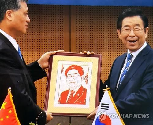 Seoul Mayor Park Won-soon (R) poses with a gift of a portrait from Ma Xingrui, governor of the southern Chinese province of Guangdong, at his office in downtown Seoul on April 5, 2019. The Chinese governor mistakenly gave the mayor a portrait of Gyeonggi Province Gov. Lee Jae-myung. (Yonhap)