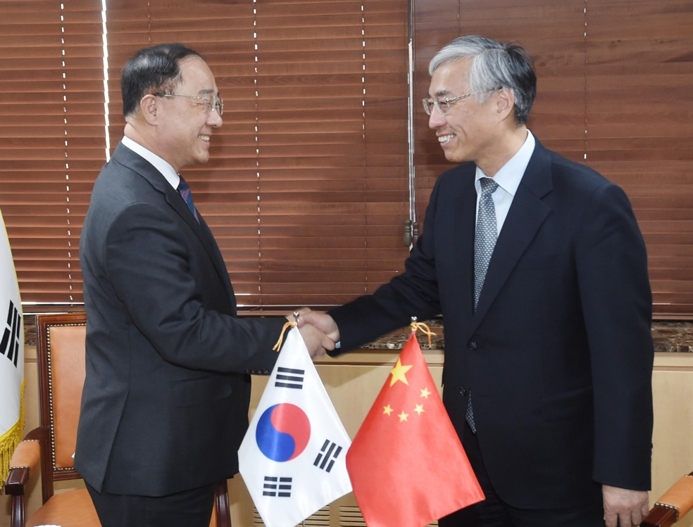 Hong Nam-ki (L), the minister of economy and finance, shakes hands with Chinese Ambassador to Seoul Qiu Guohong at a government building in central Seoul on April 19, 2019, in this photo provided by the ministry. (Yonhap)