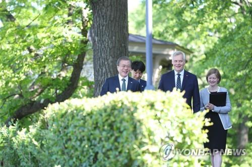 South Korean President Moon Jae-in (L) walks with Finnish Prime Minister Antti Rinne at his official residence in Helsinki on June 11, 2019. (Yonhap)