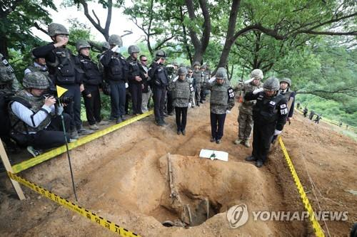 Defense Minister Jeong Kyeong-doo (2nd from R) salutes before the remains of a South Korean soldier killed in the 1950-53 Korean War inside the Demilitarized Zone (DMZ) on June 11, 2019. The remains were found during a recent excavation project on Arrowhead Ridge, a former battle site in the northern border county of Cherwon. (pool photo) (Yonhap)