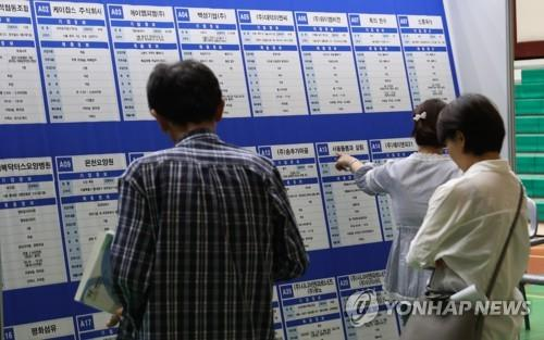 This undated file photo shows jobseekers looking at a bulletin board at a job fair in Seoul. (Yonhap)