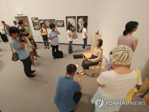 This image shows Japanese people around a statue representing comfort women on display on Aug. 3, 2019, at the Aichi Triennale 2019 in Nagoya, Japan. (Yonhap)