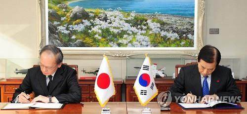 South Korean Defense Minister Han Min-koo (R) and Japanese Ambassador to South Korea Yasumasa Nagamine sign the General Security of Military Information Agreement on the sharing of military intelligence on North Korea during a ceremony at the Defense Ministry in Seoul on Nov. 23, 2016, in this photo released by the ministry. (Yonhap)