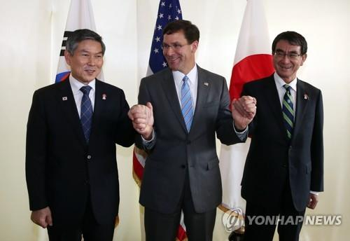 U.S. Secretary of Defense (C) hold the hands of South Korea's Defense Minister (R) and his Japanese counterpart, Taro Kono, ahead of the trilateral talks in Bangkok on Nov. 17, 2019. (Yonhap)