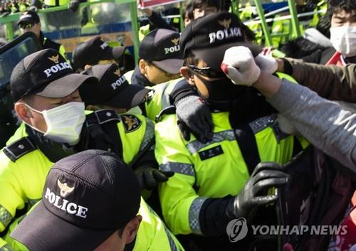 A policeman is struck in the face by Korean Confederation of Trade Unions members during their protest against a labor law revision in front of the National Assembly in Seoul on April 3, 2019. (Yonhap)