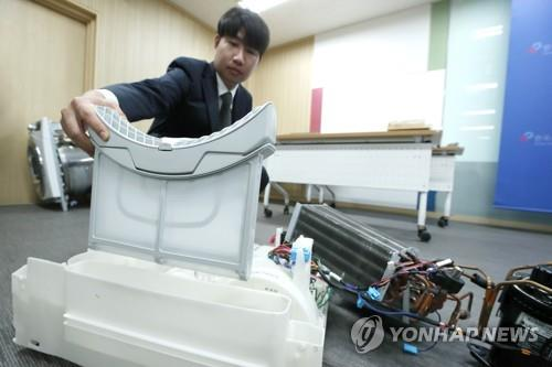 An employee at the Korea Consumer Agency shows a condenser, a key part of a clothes dryer made by LG Electronics Inc., at its office in Seoul in this file photo taken on Aug. 29, 2019. (Yonhap)