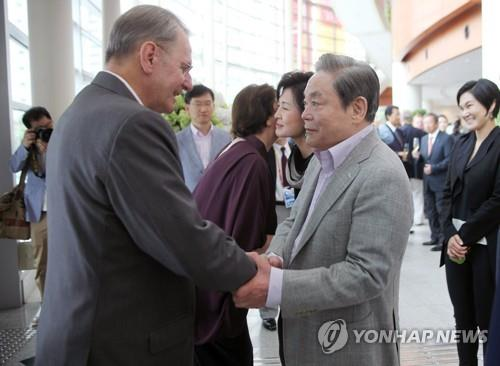 In this photo taken Aug. 28, 2011, Samsung Group Chairman Lee Kun-hee (R) shakes hands with then International Olympic Committee head Jacques Rogge at an event in Daegu, South Korea. (Yonhap)