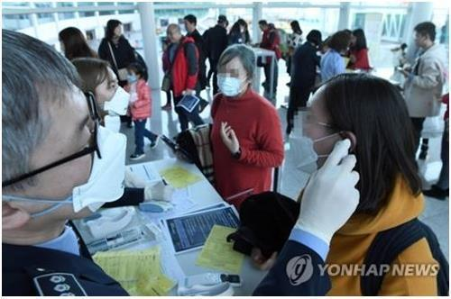 A quarantine official (L) checks a traveler for fever and other symptoms at South Korea's Incheon International Airport, west of Seoul, on Jan. 20, 2020. (Yonhap)